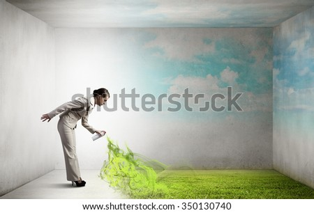 Young businesswoman spraying green grass from aerosol balloon - stock photo