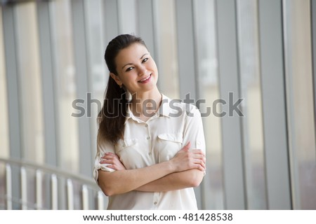 beautiful bright office. young businesswoman standing by window in office beautiful female model bright o