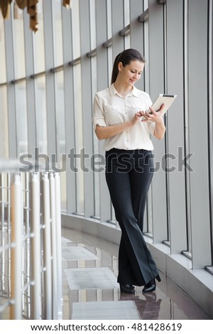 beautiful bright office. young businesswoman standing by window in office beautiful female model bright