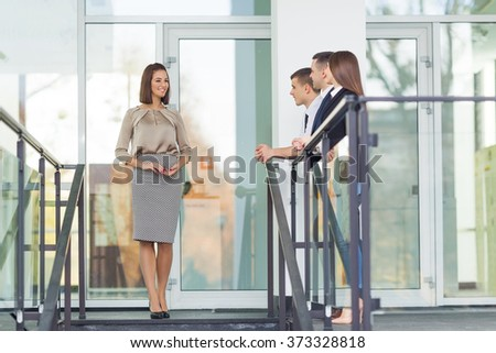 Young businesswoman standing in front of her business team - stock photo