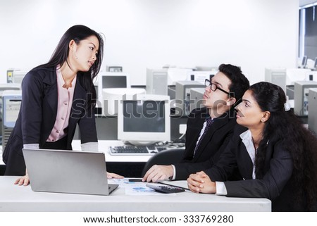 Young businesswoman standing in front of her employees and looking at them seriously and emotionally - stock photo