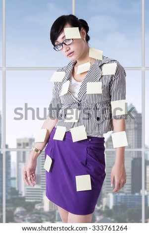 Young businesswoman standing in the office and attached empty paper notes on her body - stock photo