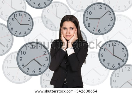 Young businesswoman stands among big clocks. Isolated on white background - stock photo