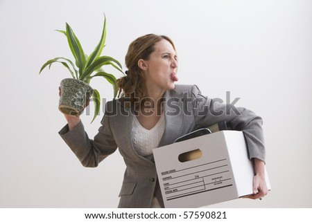 Young businesswoman sticks out her tongue while holding a plant and other office belongings. Horizontal shot.