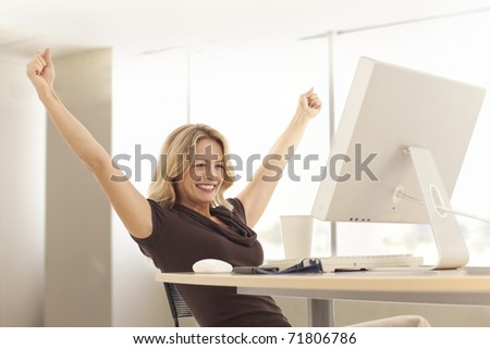 Young businesswoman stretching at desk - stock photo