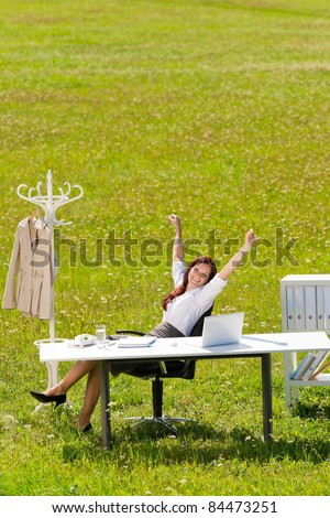 Young businesswoman stretching behind table in sunny meadow nature office