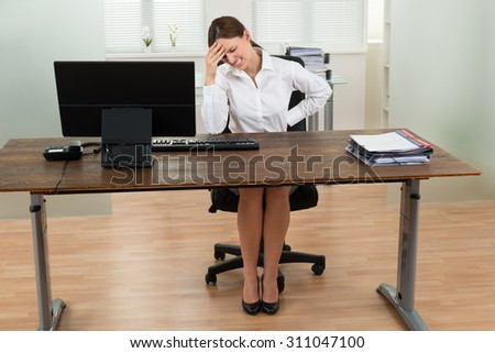 Young Businesswoman Suffering From Backache And Headache In Office - stock photo