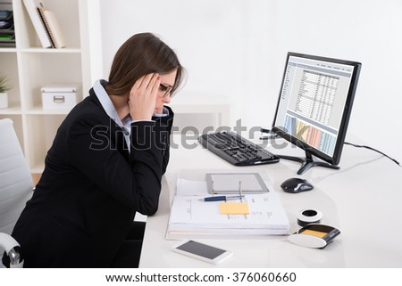 Young Businesswoman Suffering From Headache At Workplace - stock photo