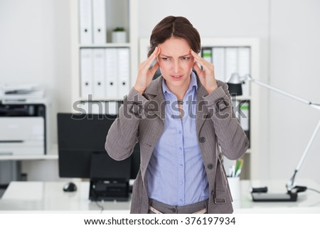 Young businesswoman suffering from headache in office - stock photo