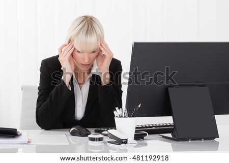 Young Businesswoman Suffering From Headache In Office