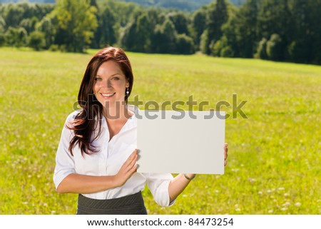 Young businesswoman sunny meadow holding aside blank advertising banner