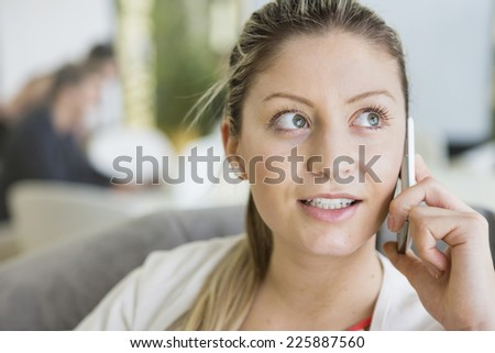 Young businesswoman talking on cell phone in office - stock photo