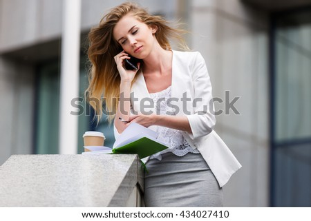 Young businesswoman talking on cellphone while walking outdoor - stock photo
