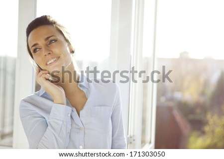 Young businesswoman talking on mobile phone while standing by window in office. Beautiful young female model in bright office. - stock photo