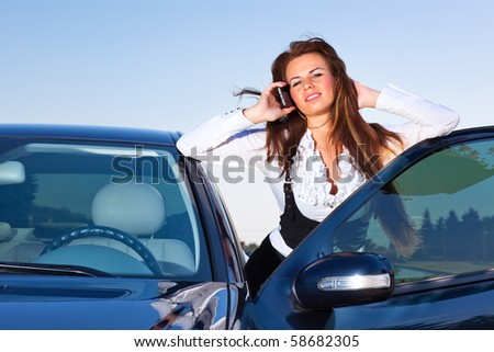 Young businesswoman talking on phone at her car. - stock photo