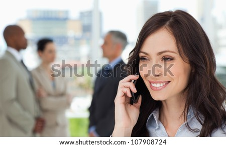 Young businesswoman talking on the mobile phone while showing a beaming smile - stock photo