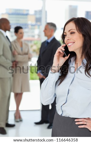 Young businesswoman talking on the phone and smiling with one hand on her hip - stock photo