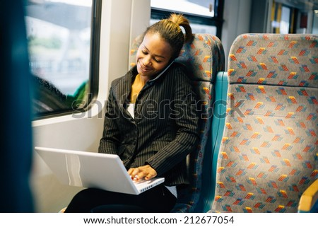 Young businesswoman talking on the phone ans using laptop on train - stock photo