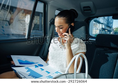 Young businesswoman talking on the phone in the back seat of the car and holding document with charts - stock photo