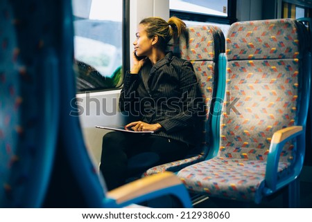 Young businesswoman talking on the phone on train - stock photo