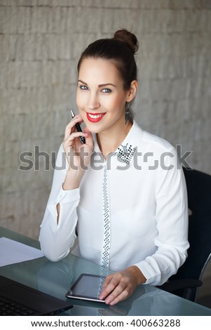 Young businesswoman teeth smile with tablet in office - stock photo