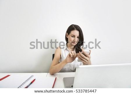 Young businesswoman text messaging through cell phone at desk in office