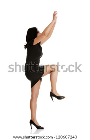Young businesswoman trying to climb a something , isolated on white background - stock photo
