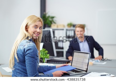 Young businesswoman turning to smile at the camera as she sits working at a laptop computer in the office watched in the background by a smiling male colleague