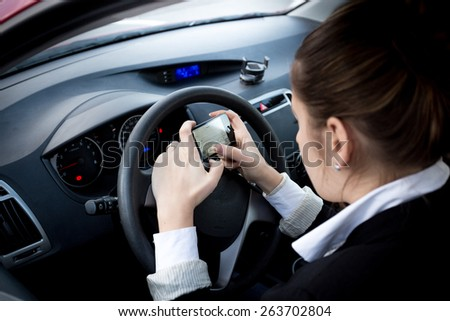 Young businesswoman typing text on smartphone at car - stock photo