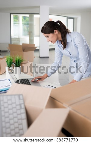 Young businesswoman using a laptop and unpacking carton boxes in her new office, new business concept - stock photo