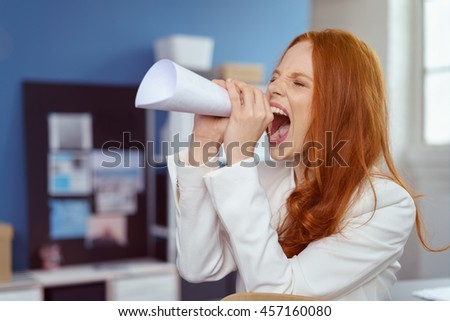 Young businesswoman using a paper megaphone in the office made from a rolled up page of paper to get the attention of a colleague - stock photo