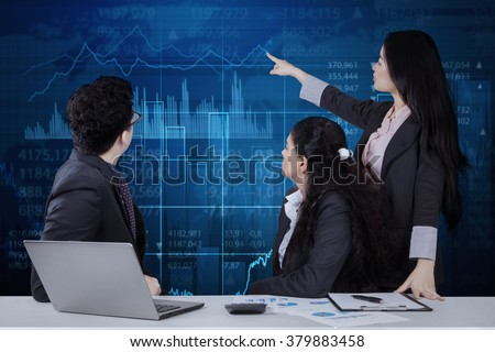 Young businesswoman using a virtual screen to explain financial statistics to her partners - stock photo