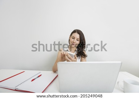 Young businesswoman using cell phone at desk in office - stock photo