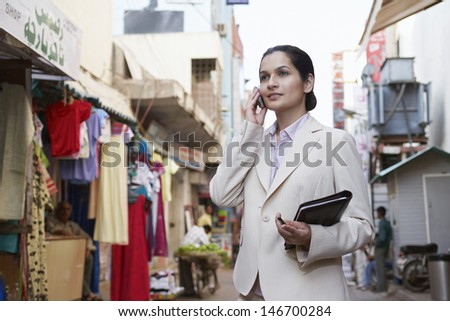 Young businesswoman using cell phone on city street - stock photo