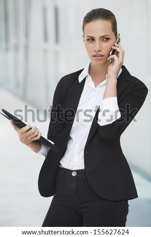 Young businesswoman using cellphone and holding digital tablet - stock photo