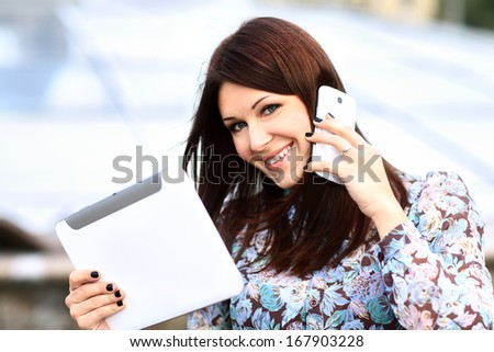 young businesswoman using digital tablet and mobile phone over building background - stock photo