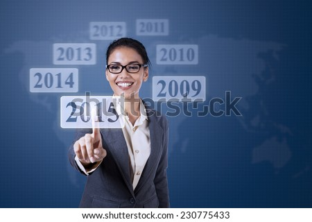 Young businesswoman using high tech monitor and select a button with number 2015