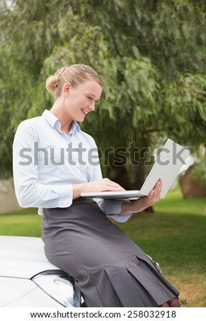Young businesswoman using laptop beside her car - stock photo