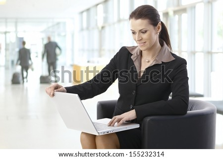 Young businesswoman using laptop computer, sitting at office lobby, smiling. - stock photo