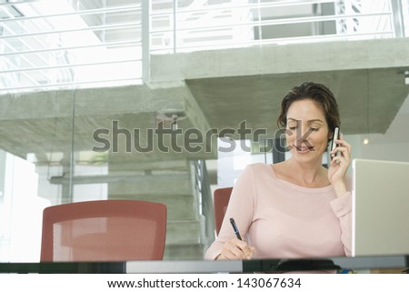 Young businesswoman using mobile phone while writing on notepad with laptop on table - stock photo