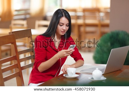 Young businesswoman using phone in coffee shop. Successful businesswoman. Young woman with phone and laptop sitting in the cafe. Attractive woman reading text message on cell telephone in cafe. - stock photo