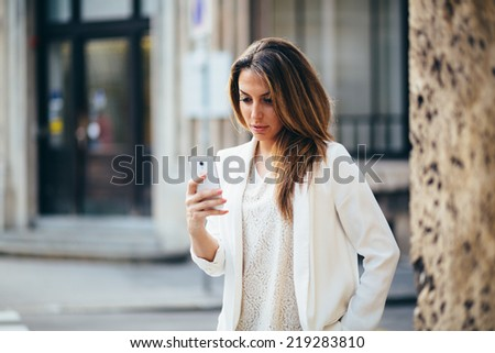 Young businesswoman using phone on the street - stock photo