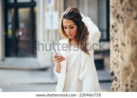 Young businesswoman using phone on the street