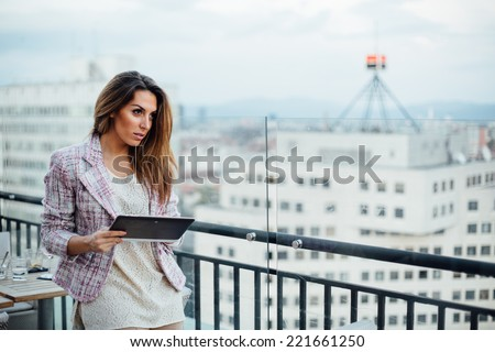 Young businesswoman using tablet computer in cafe - stock photo