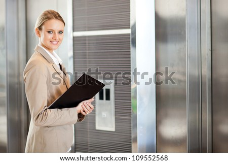 young businesswoman waiting for elevator in the building - stock photo