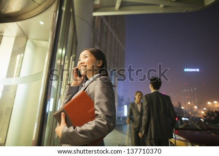 Young businesswoman walking and talking on her cell phone - stock photo