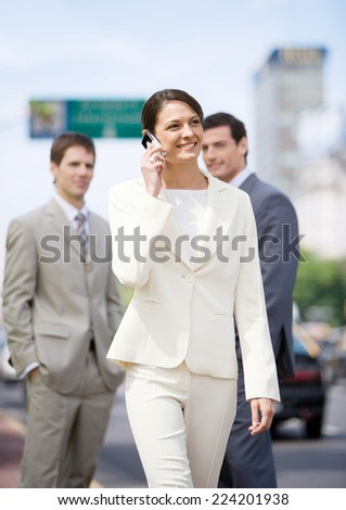 Young businesswoman walking and using cellphone while two businessmen watch in background