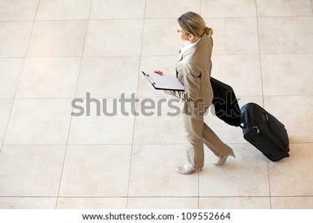 young businesswoman walking at airport with luggage - stock photo