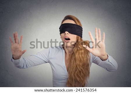 Young businesswoman walking blindfolded with hands forward isolated on grey wall background  - stock photo