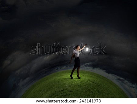Young businesswoman walking in darkness with lantern in hand